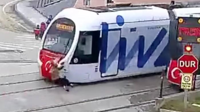 Mujer cruza delante de un tranvía hablando por teléfono y sobrevive — YouTube
